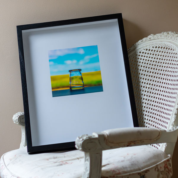 Framed color photograph by Jamie Templeton on antique chair.